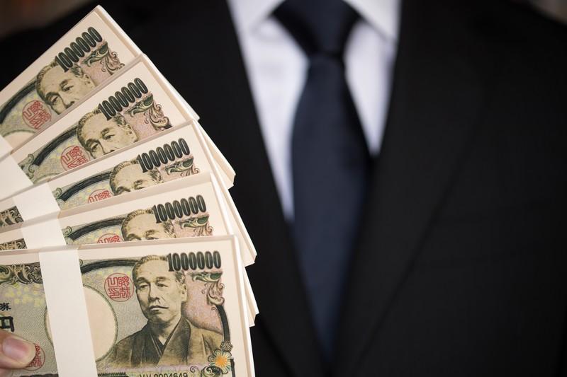 500万円の偽札をひけらかすスーツの男性
