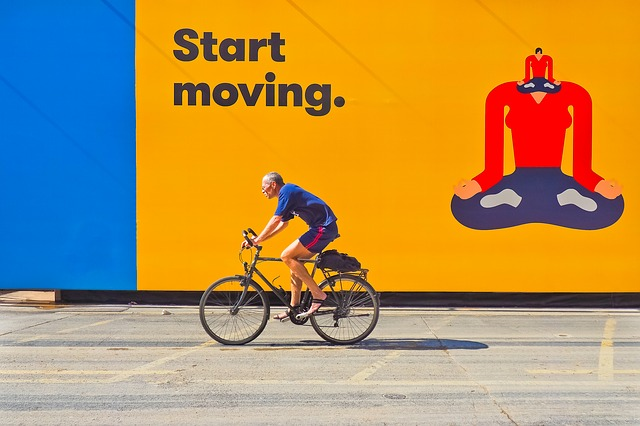 Start movingと書かれた看板 座禅する人の絵 自転車に乗る人