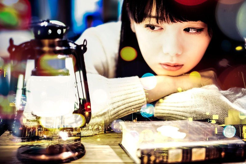 ランタンを見つめながら本を読む少女